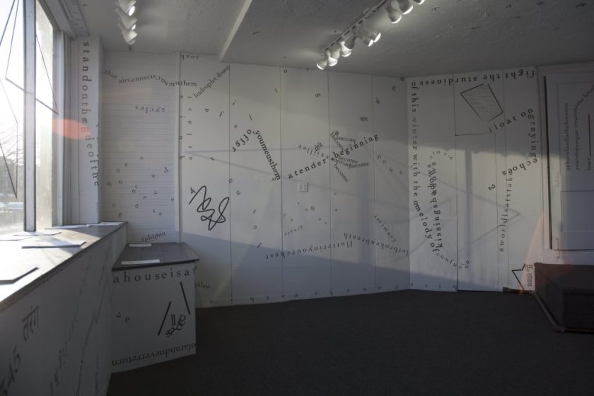 The photograph shows one full wall and parts of others as well as the front window of the gallery, with no people present. Light from the window casts shadows across the walls. Black vinyl letters are installed directly onto the white gallery walls, in the form of words and phrases in English and Hindi. Text appears in different sizes and spatial orientations (e.g., right-side up, upside-down, diagonal, vertical, and organic shapes), with some words/phrases expanded in space, condensed, or intersecting with other text. Gestural drawings—also made of black—are shown on the left-hand side of the image.