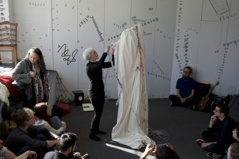 This is a still image of a performance. The performers stand in the middle of the floor, with one covered (not directly visible) in a white cloth from which a couple of colorful, braided cloths hang like ribbons or ropes. The other performer pulls or arranges one of the ribbons or ropes. Audience members are all around, leaning against a gallery wall or sitting or standing on the floor. Words, phrases, and shapes on the gallery wall and front window are visible in the background.