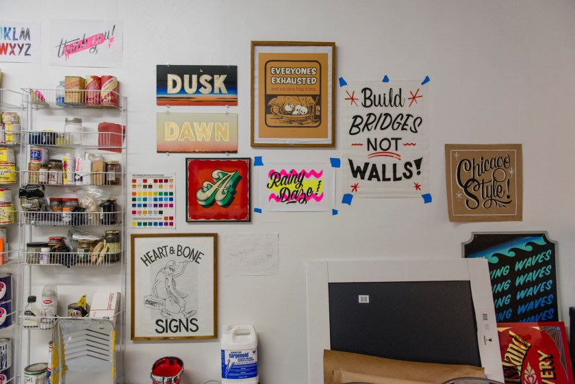 Image: Kelsey and Andrew's studio space, displaying examples of hand lettering and gold leaf work with commonly used materials and tools. Photo by Ryan Edmund Thiel.