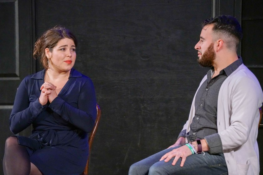 This is a medium-shot of the performers seated on-stage. Nicole looks at Devin with clasped hands, and Devin looks back with hands on lap. Behind the performers is the black wall of the stage, with a part of a black door and a black, covered window visible in the frame.
