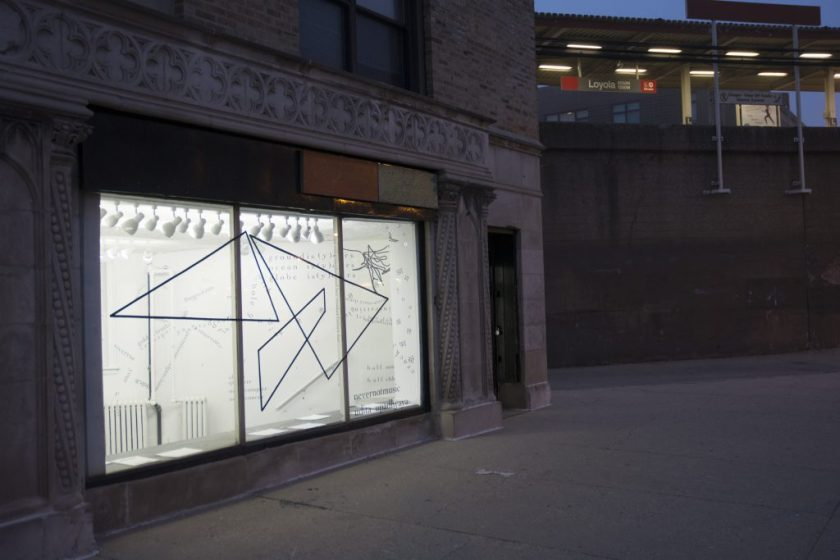 "This is an external shot of the gallery, with the CTA Red Line ""Loyola"" elevated stop in the background. It is dim outside, and the gallery's lights are on inside. Visible through the gallery's large front window (which is framed by a decorative, stone façade) is the inside of the gallery—bright white walls and fixtures, with black vinyl lettering (English and Hindi) and shapes (triangular and gestural)."