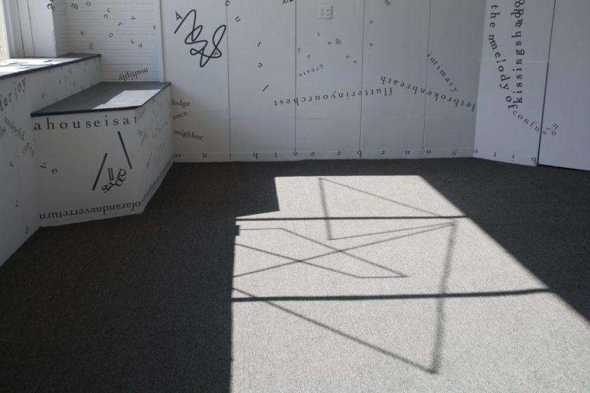 This photo shows part of the floor of the gallery, with sunlight from outside casting the shadow of the windowsill, the windowframe, and a motif of intersecting vinyl triangular shapes onto the grey rug. Black vinyl letters are installed directly onto the white gallery walls, in the form of words and phrases in English and Hindi. Text appears in different sizes and spatial orientations (e.g., right-side up, upside-down, diagonal, vertical, and organic shapes), with some words/phrases expanded in space, condensed, or intersecting with other text. Gestural drawings — also made of black — are shown on the top left-hand side of the image.