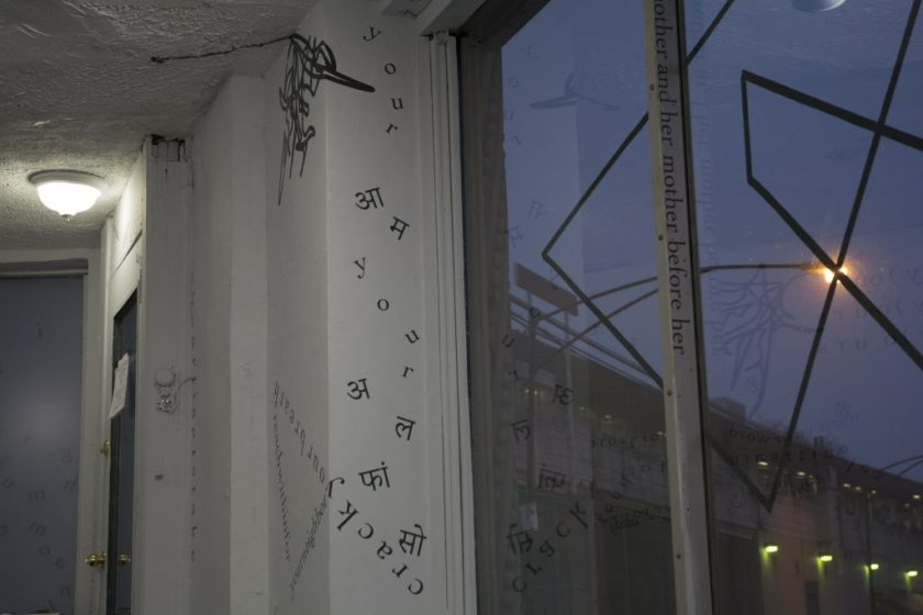 This photo shows part of the gallery's large front window (with a motif of intersecting triangular shapes made of black vinyl) from the inside, a dim sky outside, and portions of the windowframe and wall inside. On portions of the windowframe and wall inside, black vinyl letters are installed directly onto the white gallery walls, in the form of words and phrases in English and Hindi. Text appears in different sizes and spatial orientations (e.g., right-side up, upside-down, diagonal, vertical, and organic shapes), with some words/phrases expanded in space, condensed, or intersecting with other text. A gestural drawing—also made of black vinyl—is shown on the top left-hand side of the image.