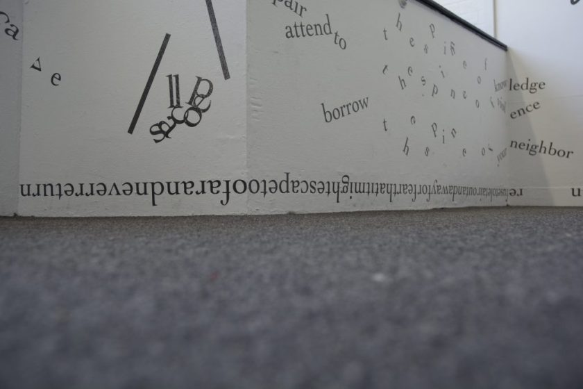 The photograph is shot from floor level and shows a low section of white gallery wall and the grey rug below. On the wall, black vinyl letters are installed directly onto the white surfaces, in the form of words and phrases in English. Text appears in different sizes and spatial orientations (e.g., right-side up, upside-down, diagonal, vertical, and organic shapes), with some words/phrases expanded in space, condensed, or intersecting with other text. A line of uninterrupted text with no space breaks runs upsidedown directly above the floor, around a convex corner.