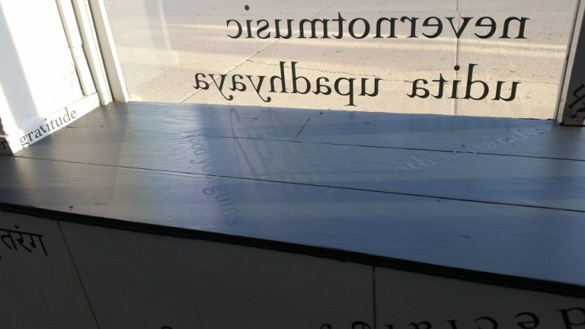 """Through the glass (at the top of the image), the words """"nevernotmusic"""" and """"udita upadhyaya"""" are visible in reverse from behind. The sidewalk is on the other side of the glass. There is black vinyl lettering on the black windowsill (including """"flood your gums""""), on the white windowframe (""""gratitude""""), and the white gallery wall below (in Hindi)."""