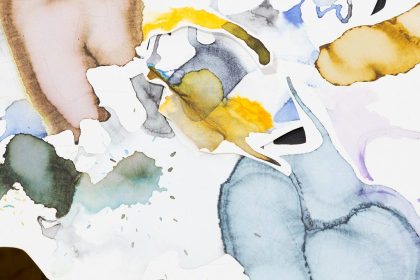 This is a close-up of part of an artwork, showing several pieces of asymmetrical white paper layered over and under each other. On the pieces of paper are abstract forms in colorful ink, and the paper is often cut just around the forms. Thin graphite lines cross a couple of papers. Between the papers, tiny bits of the black table below are visible.