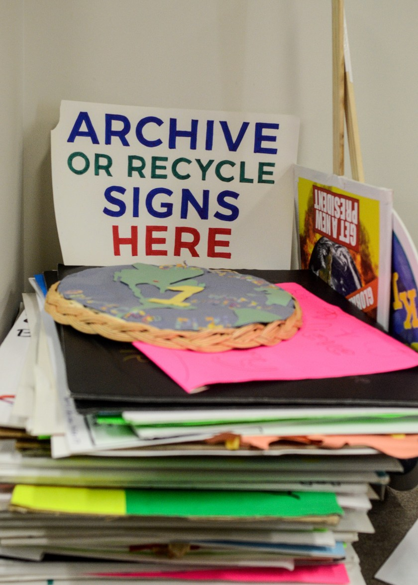 "Image: A stack of multicolored poster board signs is shown. A sign that reads ""Archive or Recycle Signs Here"" stands above the stack. One sign is the map of the world pasted onto a woven basket. Two signs with sticks attached can be seen to the right. Image by William Camargo."