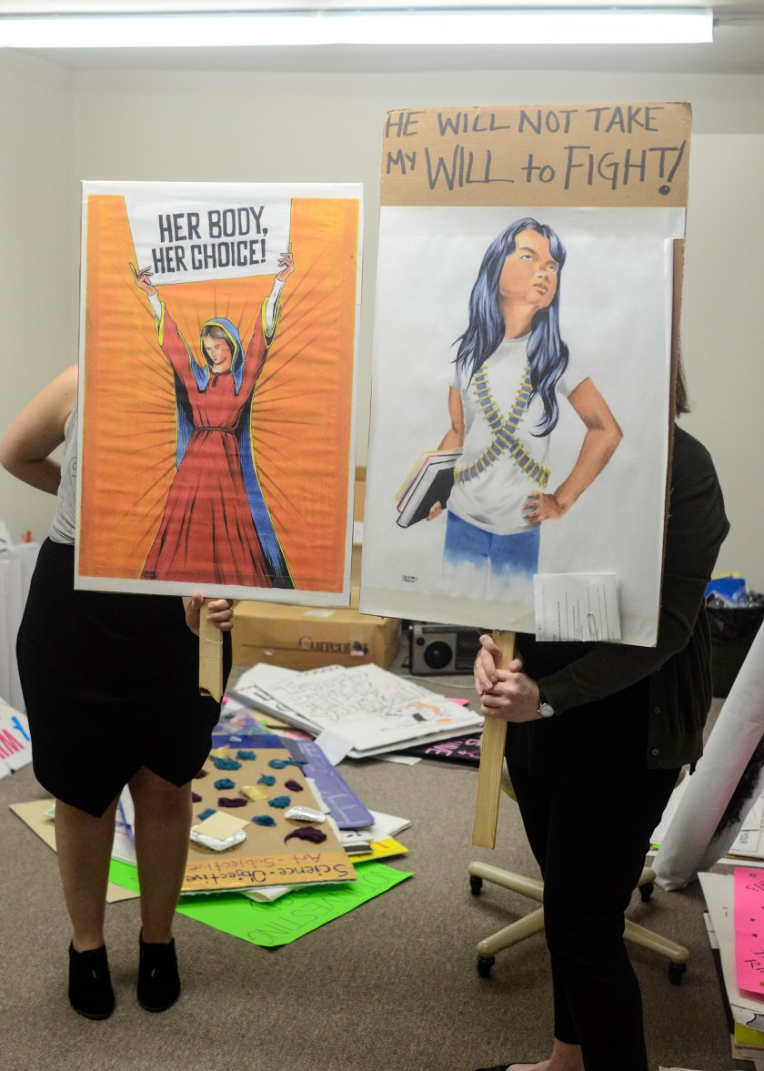 "Image: Catherine Grandgeorge and Jennifer Patiño Cervantes hold up signs in front of them. The two signs are of images made by and donated by artists Adrian Santiago-Alvarez. One shows a Virgin Mary like figure holding a sign that says ""Her Body Her Choice."" The other shows a defiant young woman holding books and wearing bandoliers under a sign that says ""He Will Not Take My Will to Fight!"" Image by William Camargo."