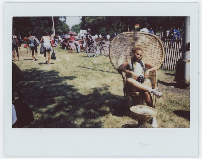 Image: Scheherezade Tillet sits in a wide-backed wicker chair on a grassy lawn full of other people, evoking Huey Newton's famous Black Panthers portrait. Image courtesy of the Museum of Vernacular Arts.