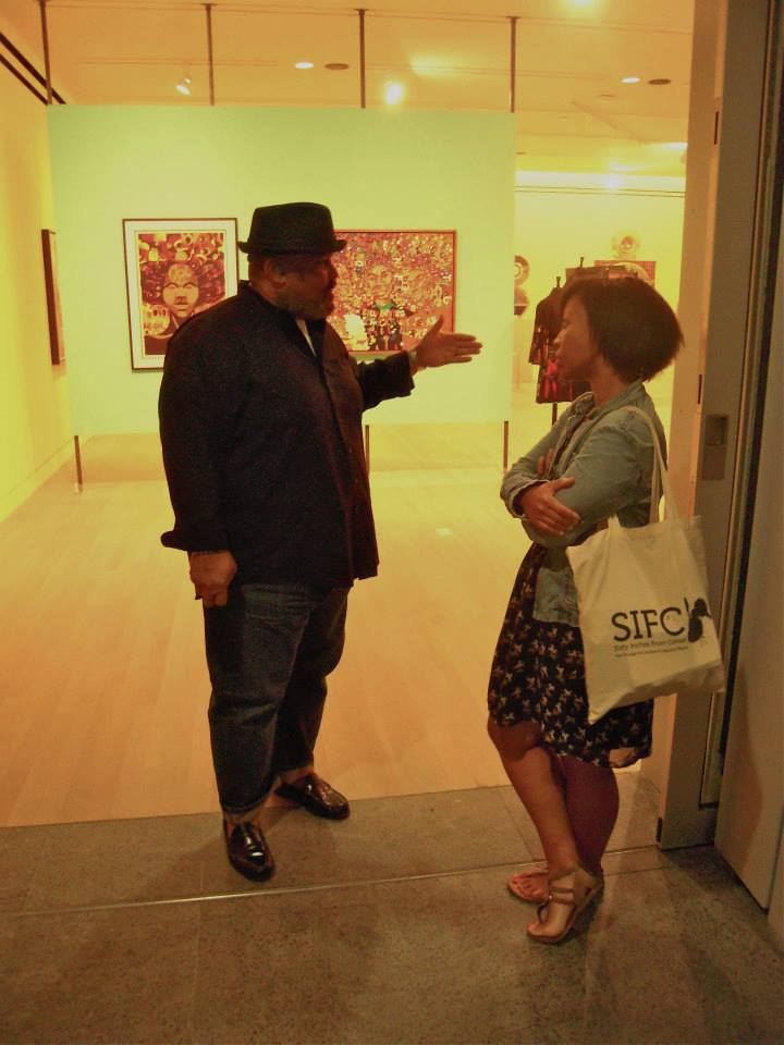 Image: Dawoud Bey and me at the Logan Center for the Arts, 2013. Photo by Ron West. An image of two people standing in the doorway of an art gallery, facing one another. The person on the left of the image is speaking, with had outstretched in front of him. The other is standing, arms and leg crossed, listening.