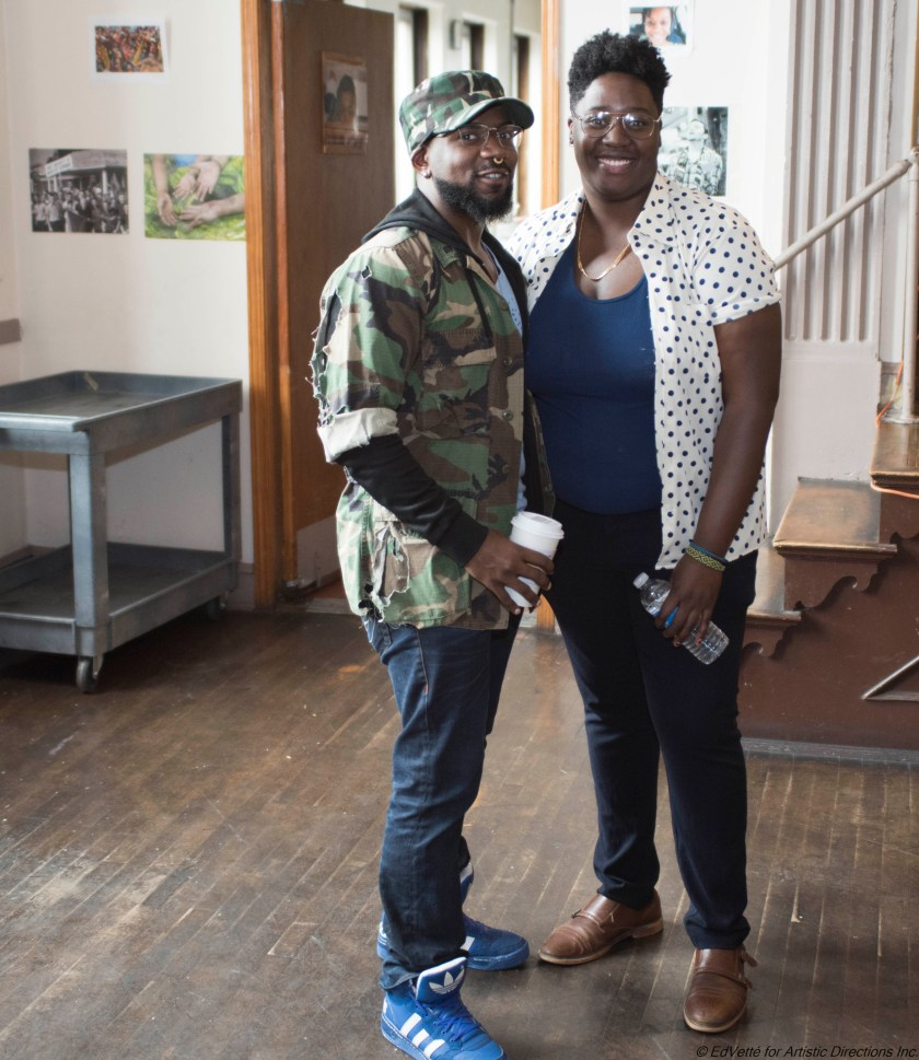 IMAGE: AnnMarie Brown stands to the left of Envisioning Justice Artistic Project Manager during Circles & Ciphers Harambee event in May. AnnMarie Brown wears a polka dot button down shirt with a blue t-shirt, black pants, and brown dress shoes. Onyx Mandelbrot wears a camouflage baseball cap, camouflage jacket, blue jeans, and blue sneakers.