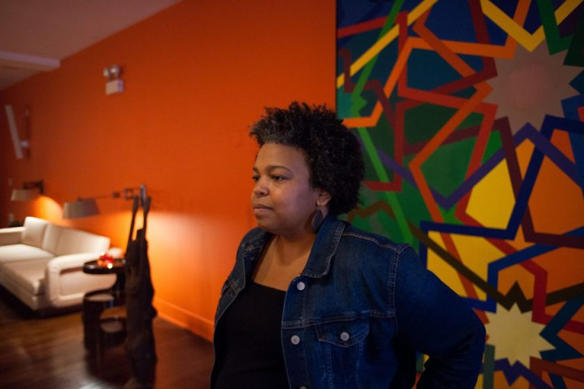 Image: Samantha Hill captured in A Johnson Publishing Story exhibition, standing in a room filled with artwork and furnishings fro the Johnson Publishing Company's archives. Photo by Tony Smith.