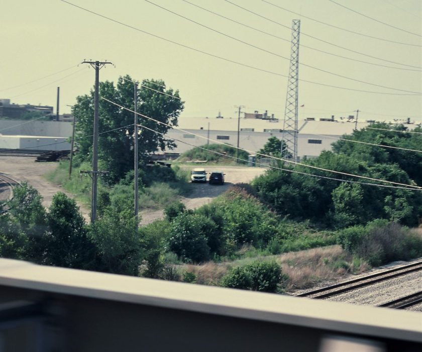 Image: On an unpaved backroad in the distance, surrounded by crisscrossing train tracks and telephone wires, two Chicago Police Department SUVs, one blue and white, one unmarked gray, sit facing opposite directions in the shade of a tree, the drivers apparently convening through their door windows. Except from this view, through the window of a passing car on the CTA Pink Line, which runs through North Lawndale, the spot is clandestine. Photo by Eric K. Roberts.
