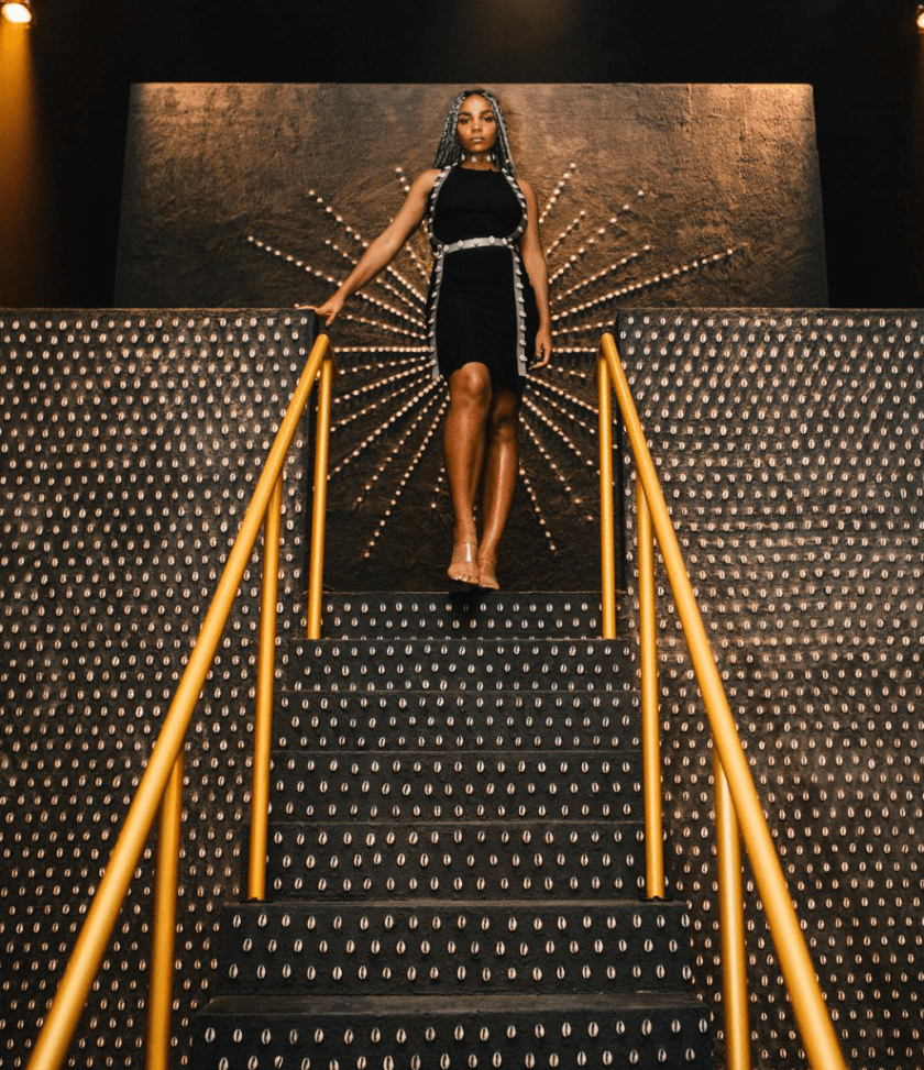 Image: Shani Crowe standing at the top of the stairs of her recent installation, Rest in Peace, at a Refinery29 event in Chicago. Behind her is a starburst made of cowry, adhered to the wall. In the foreground are the stairs and the facade of the structure, which are all patterned with cowry shells as well. The golden stair rails lead down and toward the camera. Photo from Shani Crowe's Instagram.