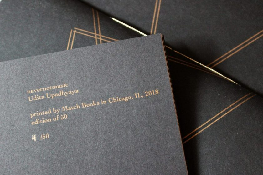 """Image: Udita Upadhyaya's book """"nevernotmusic"""" (detail). The top corner of one page is visible, with text that includes: """"printed by Match Books in Chicago, IL, 2018 / edition of 50 / 4/50."""" This writing appears in gold type except for """"4,"""" which is handwritten in gold ink. In the background, beyond that page, is part of the front cover of two other copies, with gold stitching and straight gold lines on black paper. Photo by Caleb Neubauer."""