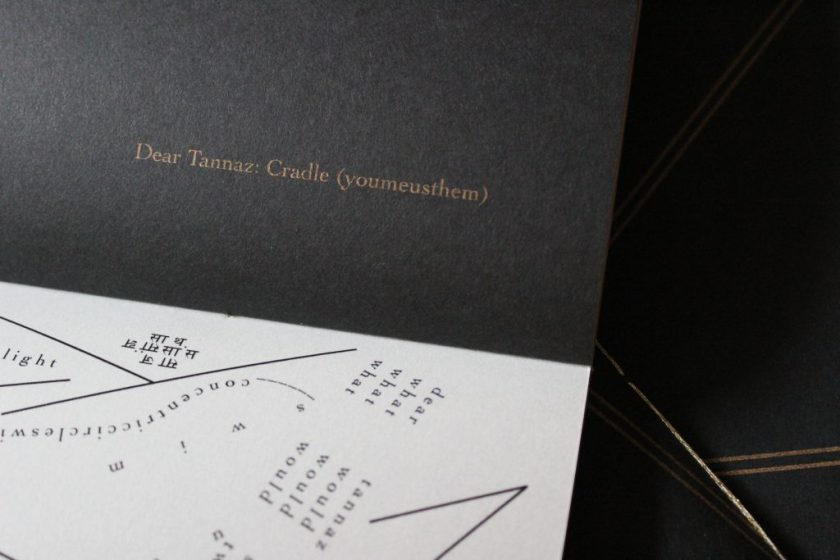 """Image: Udita Upadhyaya's book """"nevernotmusic"""" (detail), showing part of the score, """"Dear Tannaz: Cradle (youmeusthem)."""" Part of one page-spread is visible, with opaque black paper on the upper page (where the score's title appears in gold type) and with whitish vellum on the lower page (with lines, open triangles, and straight and curved lines of text in English and Hindi, printed in black ink). In the background, beyond this copy, is part of the front cover of two other copies, with gold stitching and straight gold lines on black paper. Photo by Caleb Neubauer."""