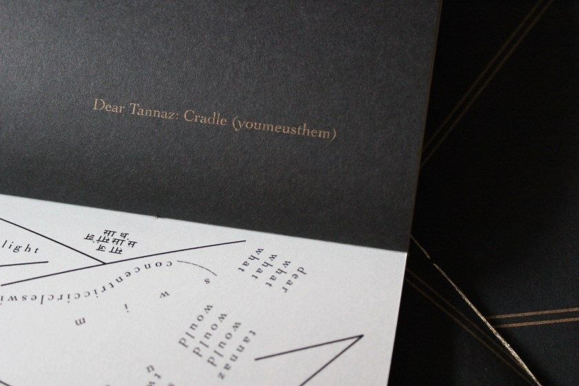 "Image: Udita Upadhyaya's book ""nevernotmusic"" (detail), showing part of the score, ""Dear Tannaz: Cradle (youmeusthem)."" Part of one page-spread is visible, with opaque black paper on the upper page (where the score's title appears in gold type) and with whitish vellum on the lower page (with lines, open triangles, and straight and curved lines of text in English and Hindi, printed in black ink). In the background, beyond this copy, is part of the front cover of two other copies, with gold stitching and straight gold lines on black paper. Photo by Caleb Neubauer."