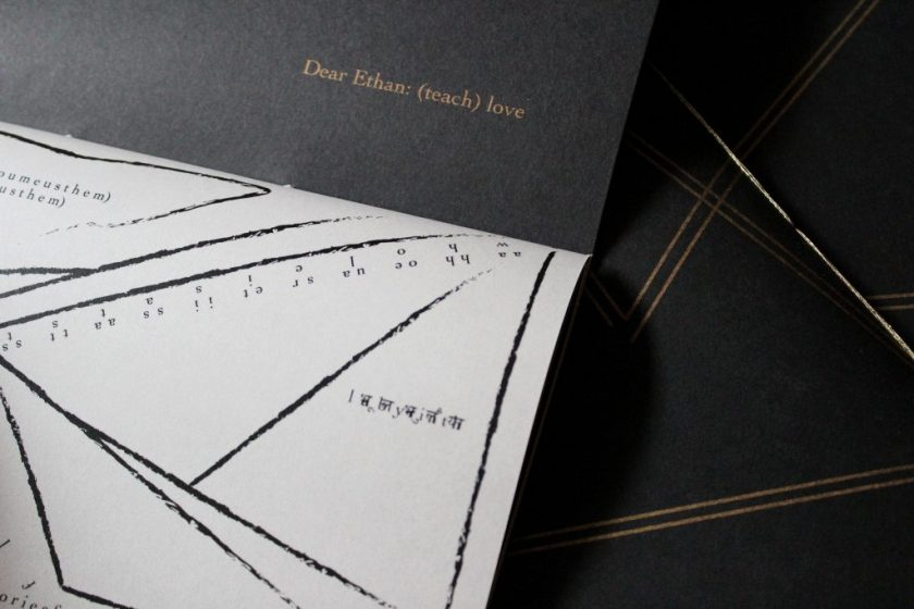 """Image: Udita Upadhyaya's book """"nevernotmusic"""" (detail), showing part of the score, """"Dear Ethan: (teach) love."""" Part of one page-spread is visible, with opaque black paper on the upper page (where the score's title appears in gold type) and with whitish vellum on the lower page (with gestural lines, triangles, and text in English and Hindi, printed in black ink). In the background, beyond this copy, is part of the front cover of two other copies, with gold stitching and straight gold lines on black paper. Photo by Caleb Neubauer."""