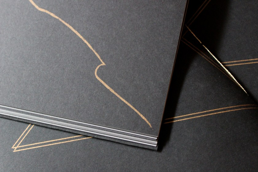 "Image: Udita Upadhyaya's book ""nevernotmusic"" (detail). Part of one page is visible, with a wavy, gold, gestural line (shaped somewhat like an elongated wave of water) descending across the black paper. In the background, beyond that page, is part of the front cover of two other copies, with gold stitching and straight gold lines on black paper. Photo by Caleb Neubauer."