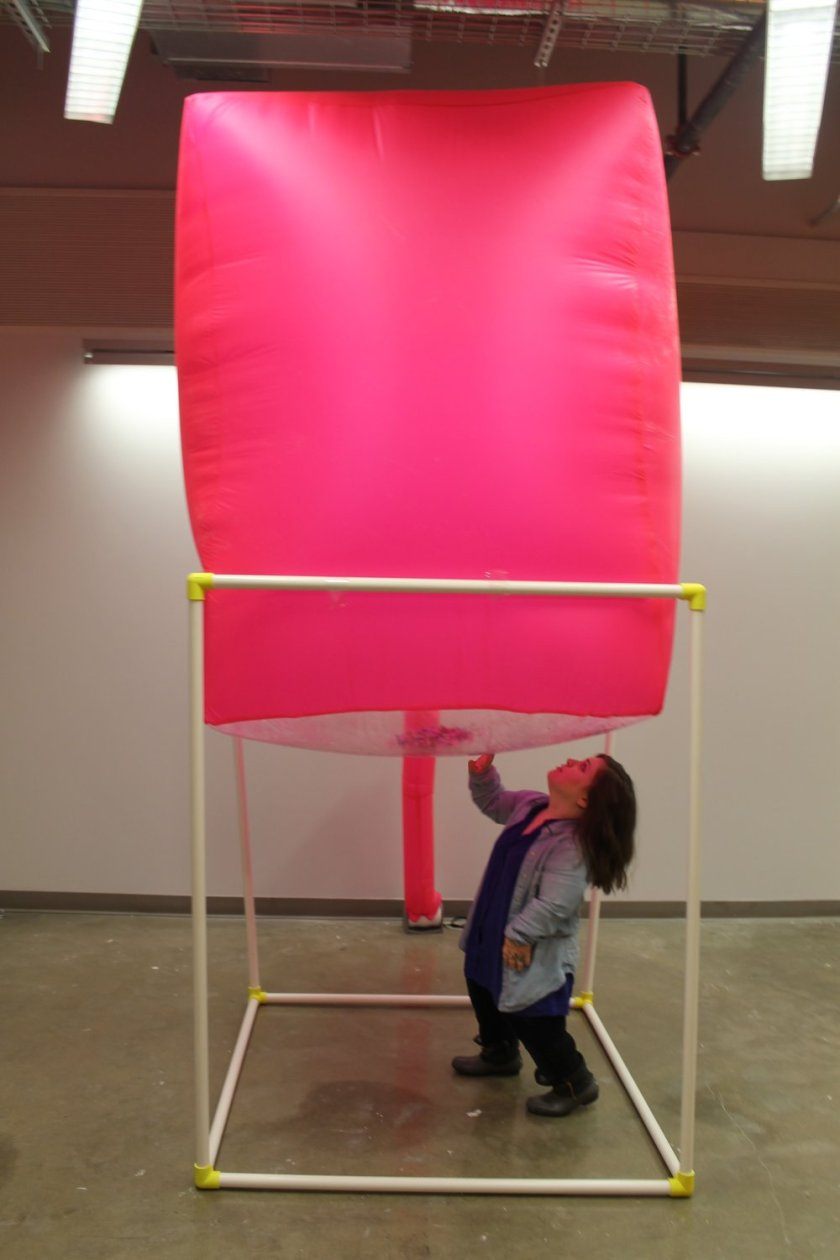 "Image: a large pink inflated cube sits atop a white PVC structure; Bri Beck stands beneath it. ""Negotiating Space: Othered by Design"" by Bri Beck, courtesy of the artist."