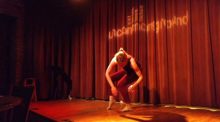 "Image: Maxine Patronik performs at a Body Passages event at Uncommon Ground. Maxine dances barefoot on a wooden stage, with ""uncommonground"" projected on the maroon curtain behind her. She leans forward, with her body bent at the hips, knees, and elbows. She wears a dark top and maroon leggings. Photo courtesy of the artist."