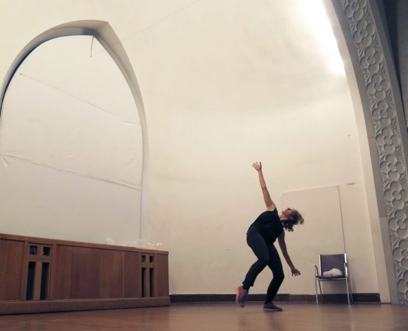 Image: Maxine Patronik rehearses on-stage at Chicago Danztheatre. Her body faces front. Maxine appears mid-motion, leaning her body far to her left, stretching her arms toward the floor and the ceiling, and looking up at the ceiling. She balances on her left foot, with her right foot pointed and off the floor. Both knees are slightly bent. Maxine wears a black tank-top and black pants. Photo by Marya Spont-Lemus.