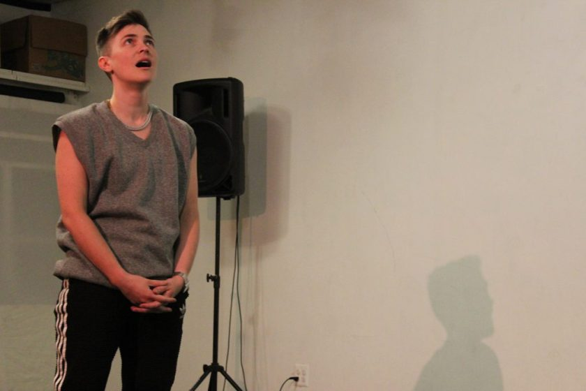 """Image: Nora Sharp performs in response to the score """"Dear Aron: (Destroy) Armor."""" On the left side of the image, the performer stands with hands folded, looking up at the ceiling and singing. On the right side, part of Nora's shadow is visible, cast on the wall. The artist wears a grey sleeveless shirt and black athletic pants with white stripes. Photo by Caleb Neubauer."""