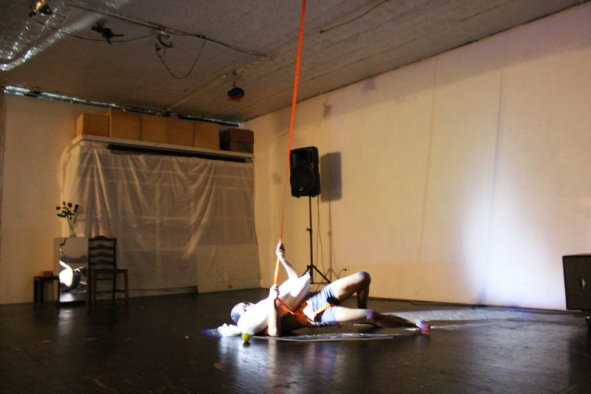 """Image: Regin Igloria performs in response to the score """"Dear Regin: SOAK (in silence)."""" Regin lies on the floor of TriTriangle, lit by a spotlight. Regin is barefoot and wears a swim cap, goggles, and spandex shorts. A sandbag lies across Regin's chest. The artist reaches his arms around the sandbag to grip an orange strap that hangs from the ceiling, as he pushes his hips off the floor. Photo by Caleb Neubauer."""