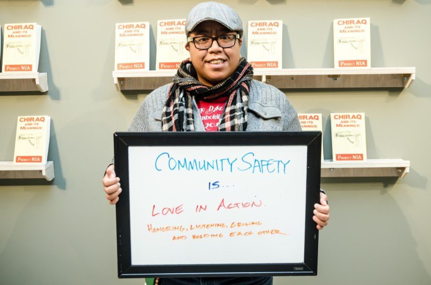 """Image: A person of color stands in front of a wall with shelves that have pamphlets with the words """"CHIRAQ And Its Meaning(s)"""" by Project NIA. This person holds a dry-erase board with """"Community Safety Is… Love in Action. Honoring, Listening, Growing, and Holding Each Other."""" in the center. Photo courtesy of the artist."""