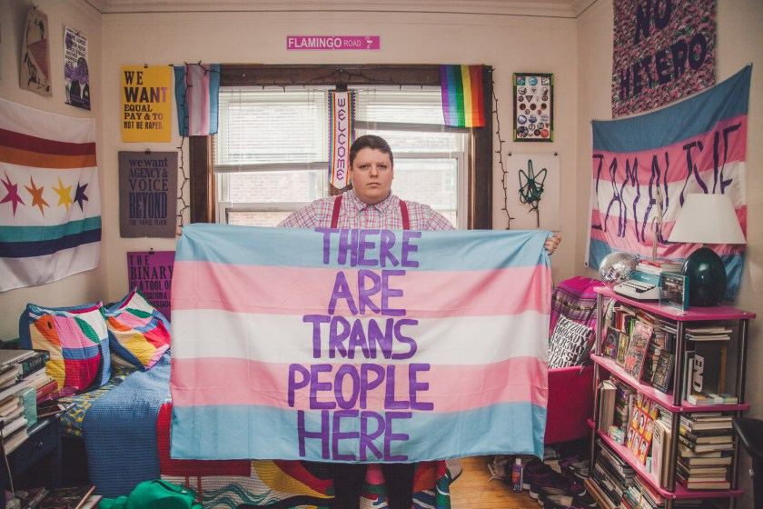 "Image: H. Melt holds open a blue, pink, and white banner, the transgender pride flag, that says ""There are trans people here"" in purple letters in their apartment. Their bed, a bookshelf, and several other printed banners and signs can be seen in the background. Photo by Ally Almore."