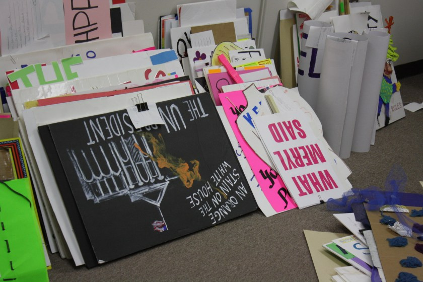 """Image: A stack of protest signs from the Chicago Protest Collection leans against a wall in the Newberry Library. In the front, one sign says """"What Meryl Said"""" and another says """"An orange stain on the White House."""" Photo by Hannah Siegfried."""