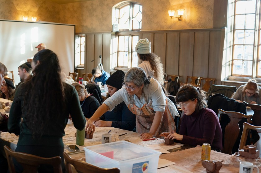Image: Nicole Marroquin (standing at center, with shirt sleeves rolled up) leads a ceramics workshop at Hull House in November. She is surrounded by participants sitting at tables molding clay into the shapes of buildings. Photo courtesy of Jane Addams Hull-House Museum / Jesse Meredith.