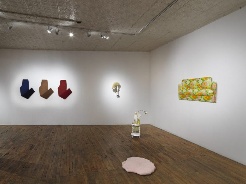 Courtesy of the artist. Gallery view of the exhibition where five pieces are seen. The pants are on the left side, along with a sculpture in the center, and a couch piece on the right side. In the middle are two smaller pieces by Nico and Lauren.