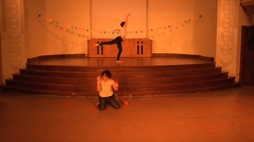 """Image: Maggie Robinson and Allison Sokolowski performing in """"I Am."""" In the foreground, Maggie kneels on the floor, holding up strands of red yarn, which is also strewn across the floor. In the background, Allison stands onstage in an arabesque, also holding up red yarn. Both performers are barefoot and wear white t-shirts and jeans. The stage is bathed in warm orange light and has a string of colorful paper suspended across it. Still from a video by John Borowski."""