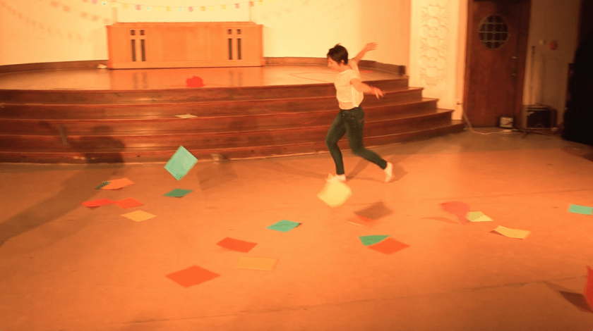 """Image: Allison Sokolowski performing in """"I Am."""" In this long shot of the performance area, Allison runs with arms spread as colorful pieces of paper fall through the air and onto the floor. A shadow of Maggie in a similar pose (off-camera) is slightly visible. The performance space is bathed in warm yellow-orange light. Still from a video by John Borowski."""