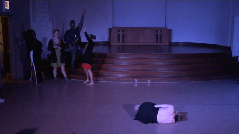 """Image: Carly Broutman and Jae Green performing in """"Wax."""" Carly lies on the floor in a ball in the foreground, her back to the camera. In a far corner, Jae and three guests celebrate, smiling, yelling, holding beverages, and/or throwing arms in the air. The lighting is dim and cool (blue-purple). Still from a video by John Borowski."""
