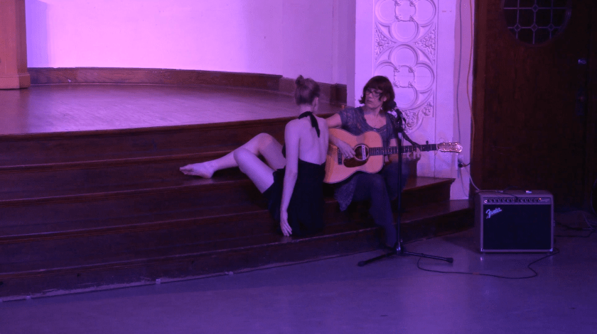 """Image: Carly Broutman and Michelle Shafer performing in """"Wax."""" This slightly closer shot shows Carly and Michelle sitting on the stage steps, turning to look at each other. Carly's back is to the audience and, though her back is positioned straight-up, her legs are folded or extended onto higher stairs than where she is sitting. Michelle holds an acoustic guitar and sits more commonly, with one foot on a lower step and another on the floor. The lighting is dim and pink-purple. Still from a video by John Borowski."""