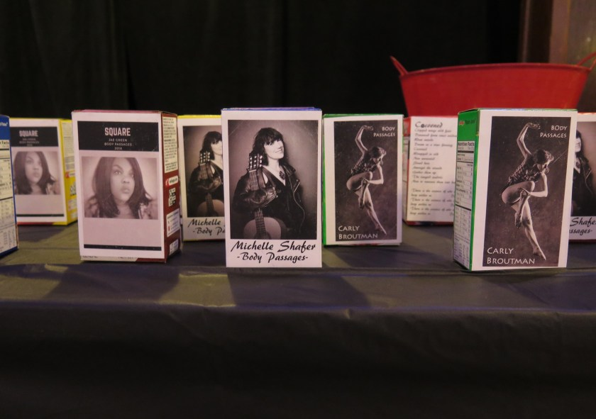 """Image: The interactive installation related to Carly Broutman, Jeanette """"Jae"""" Green, and Michelle Shafer's performance """"Wax."""" This is a close-up image of a table with a black tablecloth, on which several single-serving cereal boxes sit, each stickered on one side with a black-and-white photograph of a group member. Visible in the background are the back of one box, including lyrics for """"Cocooned,"""" and a red bucket. Photo by Marya Spont-Lemus."""