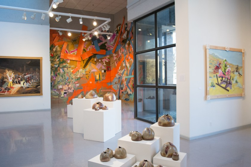 Installation shot of the MA Exhibition in Heuser Art Center at Bradley University. Ceramic pieces by Natalie Zelman are in the foreground. Framed oil paintings on the walls to the left and right by Jack Crouch. A large mixed-media painting installation hangs on the wall in the background.