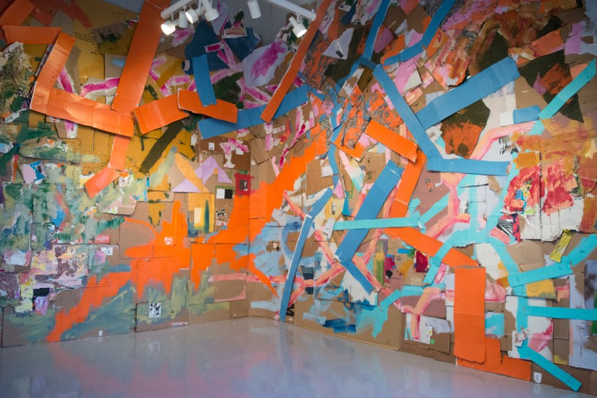 A large floor to ceiling painting installation by Peter Ahart, titled Portrait of an American Solider, hangs in the back of the gallery. The piece is a painting on cardboard, fabric, and collage paper. Orange and blue marks wind through the painting that spans three walls.