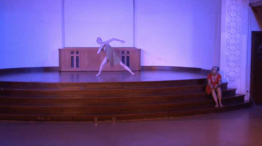 "Image: Maxine Patronik and Lani T. Montreal performing in ""Blood Memory."" Lani sits on a stage step on the right side of the image, speaking to the audience. Maxine dances in the center of the stage, lunging to one side and swinging arms as she looks up. Both performers are barefoot and wear simple knee-length dresses, Lani's red and Maxine's olive green. The lighting is dim and cool (blue-purple). Still from a video by John Borowski."