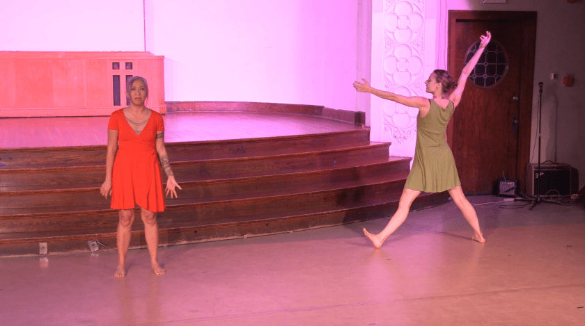"""Image: Maxine Patronik and Lani T. Montreal performing in """"Blood Memory."""" They stand by the stage, several feet apart. Lani faces the audience, speaking, with one palm held open. Facing Lani, Maxine's face is in profile to the camera; she extends her limbs in an """"x"""" shape, with her back slightly arched. The lighting is bright with pink-purple tone. Still from a video by John Borowski."""