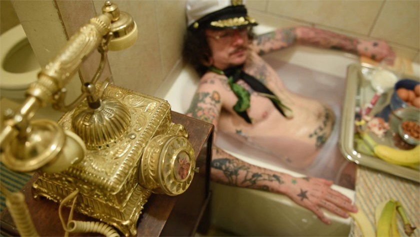 """Image: Film still from """"Sextra Curricular Activity"""", featuring actor Jack W. Cooper. In this scene, Jack's character receives a prank phone call while taking a hot soak in the tub and enjoying some light snacks. Photo courtesy of Heather Raquel Phillips."""