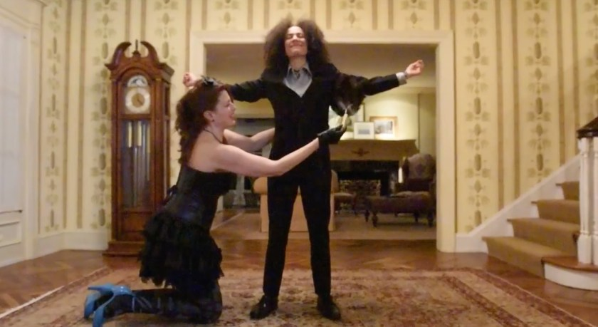 "Image: Film still from ""Thirst Trap"" featuring actors Weezy Carpino (on knees) and Monique Ligons (standing). Here we see Weezy feather dusting Monique in her opulent estate as she prepares for a special dinner date. Photo courtesy of Heather Raquel Phillips."