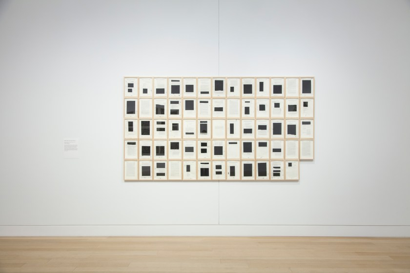 Image: Bethany Collins, Southern Review 1985 (Special Edition), 2014-15 [installation view]. 64 sheets fill a 13x5 panel with the lower-rightmost square removed. Each sheet is filled with blacked-out squares covering whatever text might appear on the page. Image courtesy of DePaul Art Museum.