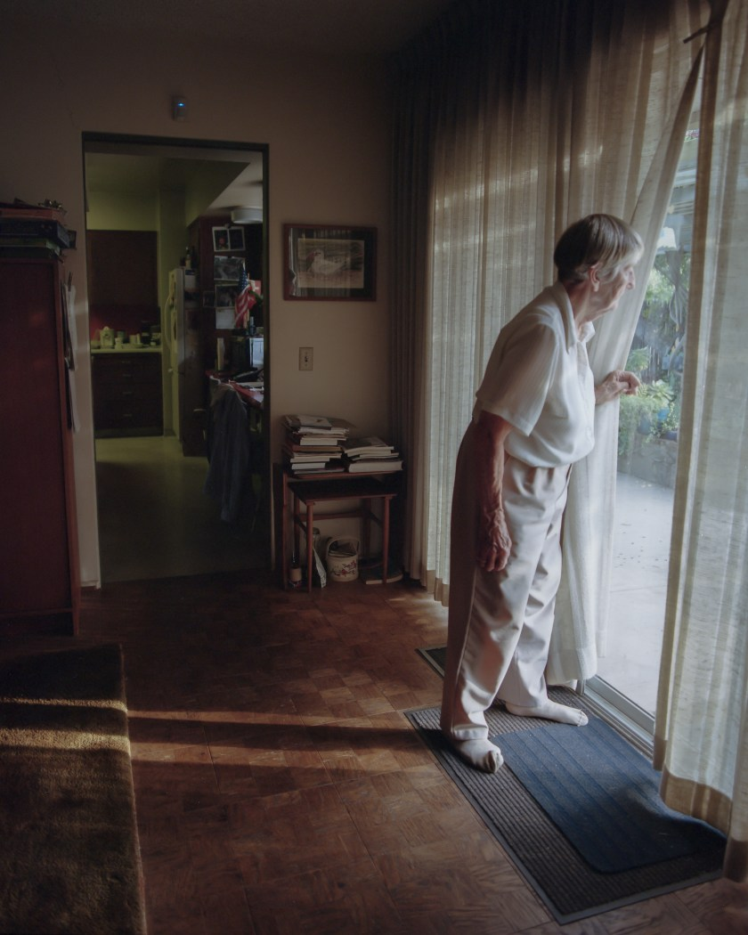 Annamarie Mitchell (Mitch'sgrandmother) peers through her window that was once shattered during a robbery. She now fears that a similar burglary will happen again and will occasionally check her backyard for trespassers. San Marino, California. Courtesy of Mitch Buangsuwon.