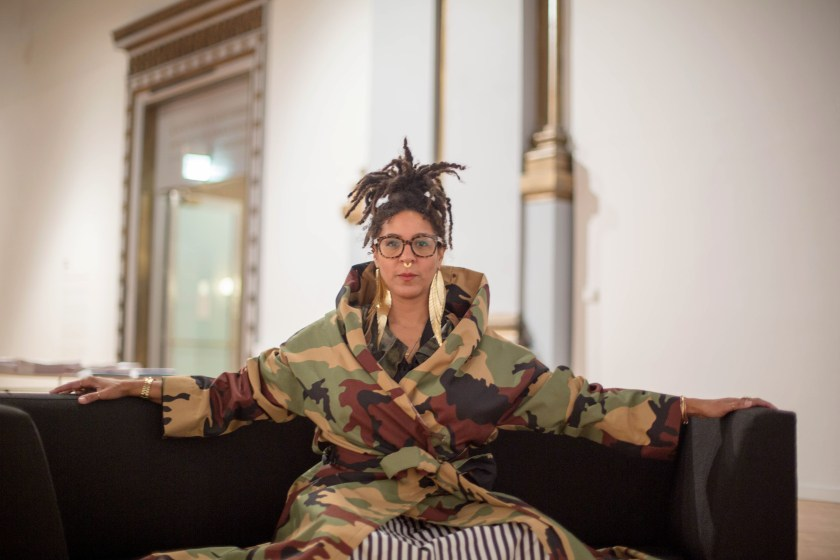 "Image: D. Denenge Duyst-Akpem wearing the garment ""The Camo Coat, part of the Osanyin Commemorative Project,"" and sitting on a black sofa in the ""African American Designers in Chicago"" exhibition at the Chicago Cultural Center. Photo by Ireashia Bennett."