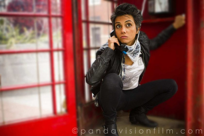 """In this photo, Fawzia (as the character Kam Kardashian) crouches low inside a red phone booth. Plants, a building, and daylight beyond are visible through the phone booth's glass windows and open door. Fawzia (as Kam) wears a black leather jacket, white shirt, tight black pants, and black boots, as well as a white and black bandana around her neck. She holds the phone receiver to her face and looks off-camera with eyebrows raised. In the bottom right-hand corner of the image it reads """"(c) pandavisionfilm.com."""""""