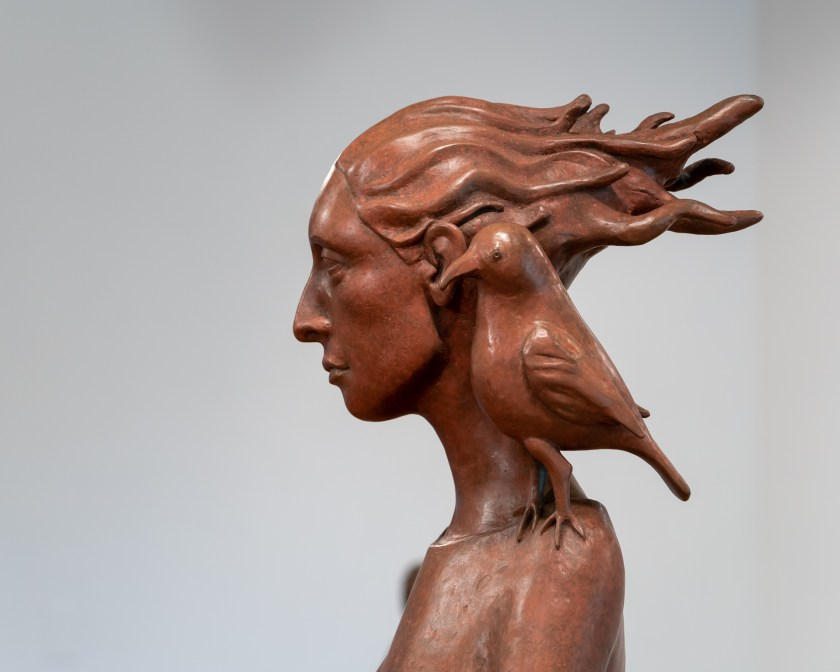 "Image: Patricia Whalen Keck ""The Pedestrian"" (Detail) Bronze. Profile of a woman with her hair blowing behind her with a bird placed upon her shoulder. Photo Courtesy of the Artist."