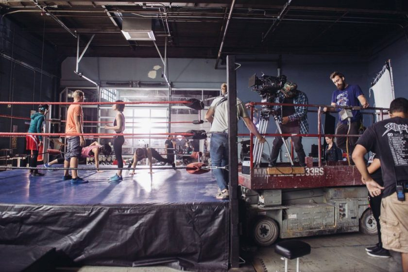 """This image shows the film """"Signature Move"""" in production in a large open room with exposed piping. On the left-hand side of the image is a fighting ring, in which Zaynab (played by Fawzia Mirza) and other characters in workout clothes stretch and talk. Zaynab wears a tight green hoodie with red and white shorts over black tights. On the right-hand side of the image are members of the production crew, who are operating the camera, holding wires, or looking on. The camera operator and another person stand on a scissor lift with the camera and camera tripod."""